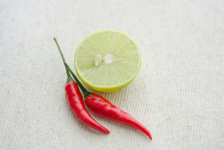 Lime and hot pepper sit beside one another as ingredients in a snake repellent recipe.