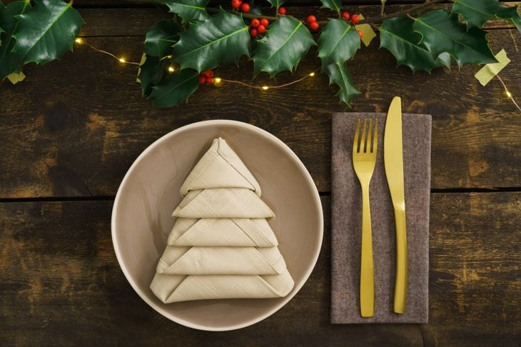 A napkin in a whimsical Christmas tree fold