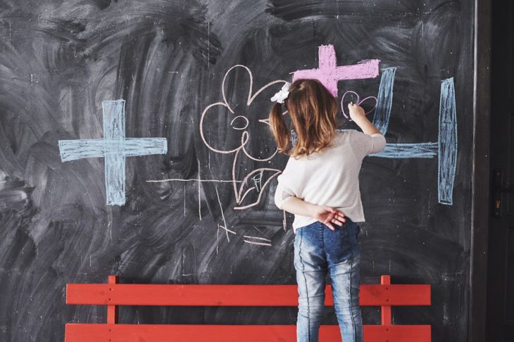 A little girl writing on a chalkboard wall