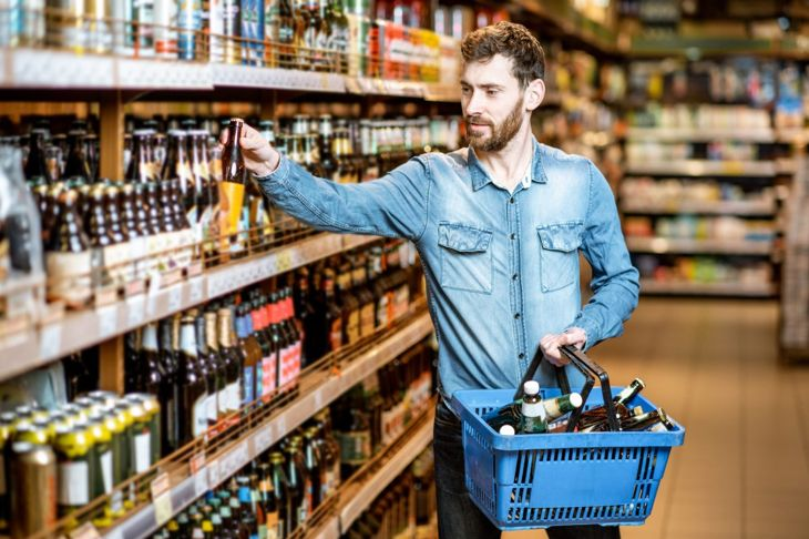 A man filling a shopping cart with beer