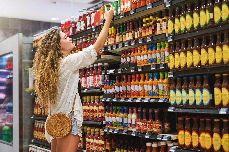 A woman shopping reaching up to the top shelf