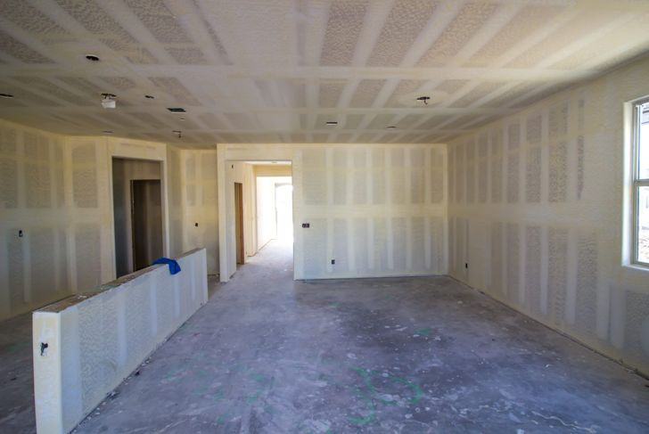 View of a room that has the drywall installed where the seams have been covered, sanded but not painted.