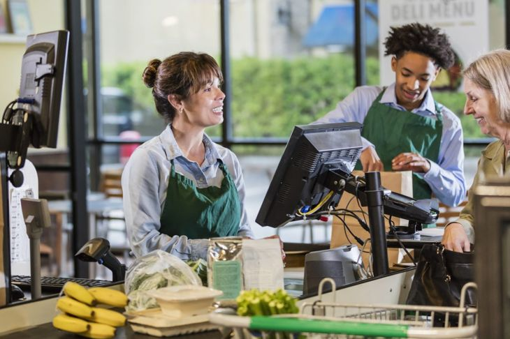 A female customer engaging with a cashier and grocery bagger
