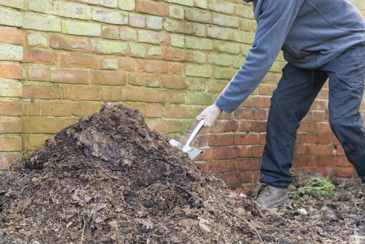 Turning a compost pile by hand.