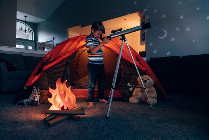 A young boy looking through a telescope in a playroom