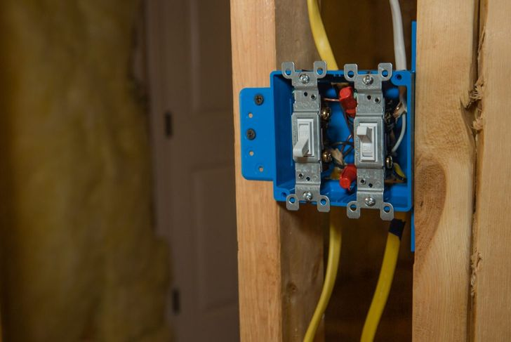Picture of a light switch box installed during the framing of a house to show how it is connected to a stud.