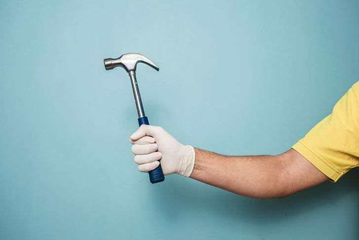 Picture of a hammer in a man's hand and a wall.