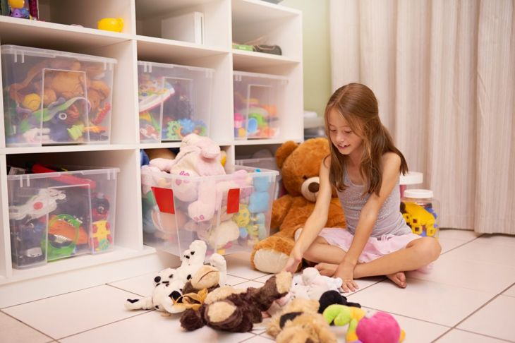 A child playing with stuffed animals next to clear bins