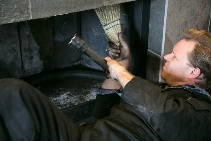 Chimney sweep cleaning a fireplace