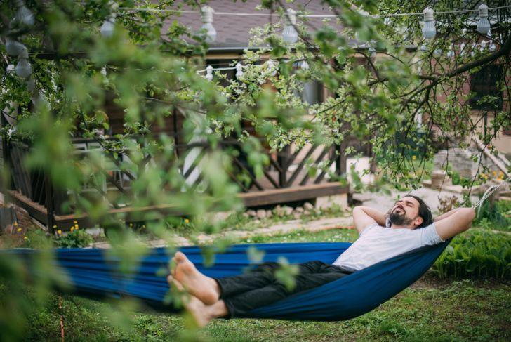 man in backyard hammock