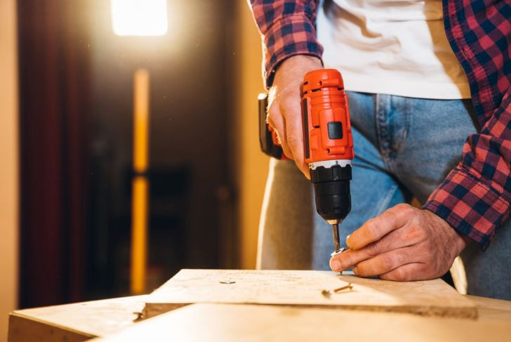Man fastening boards with drill