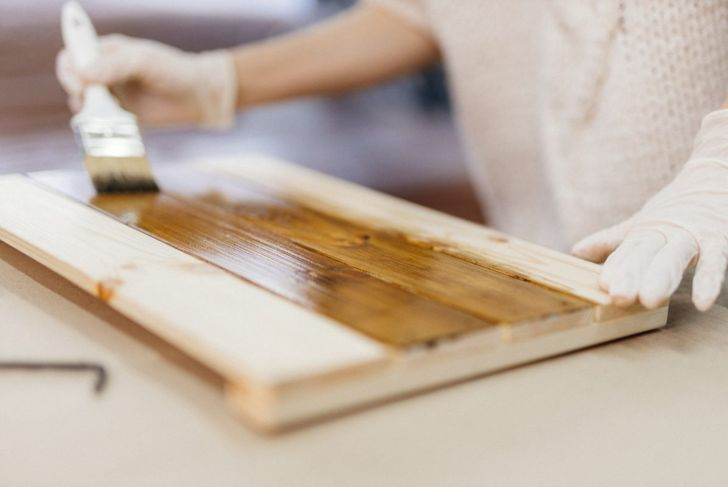 Woman staining a board