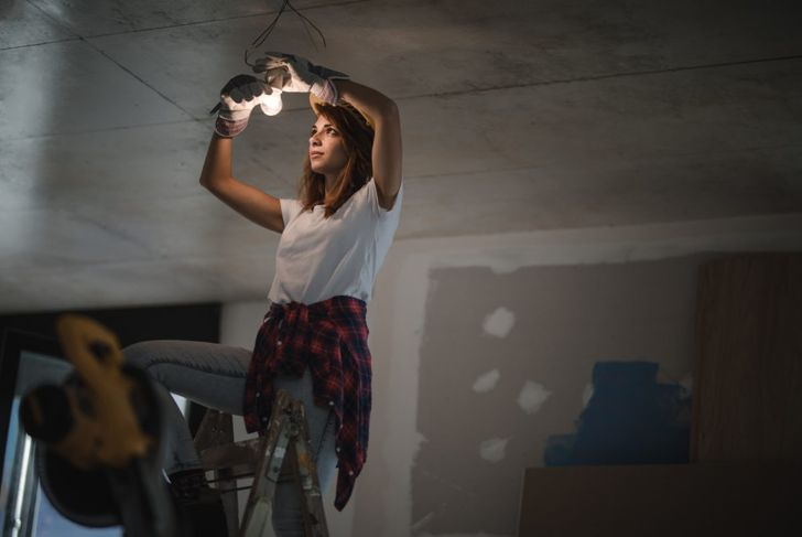 Woman working on overhead light