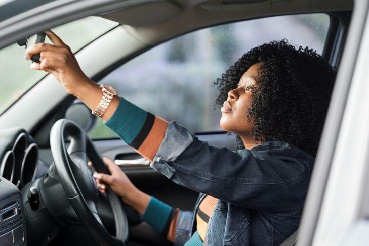 Woman looking in rearview mirror