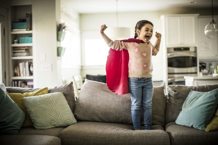 Small girl standing on couch