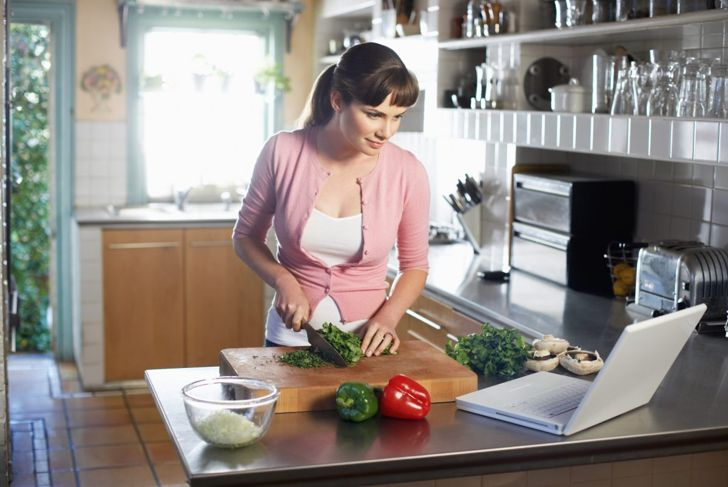 Woman cooking while reading a recipe
