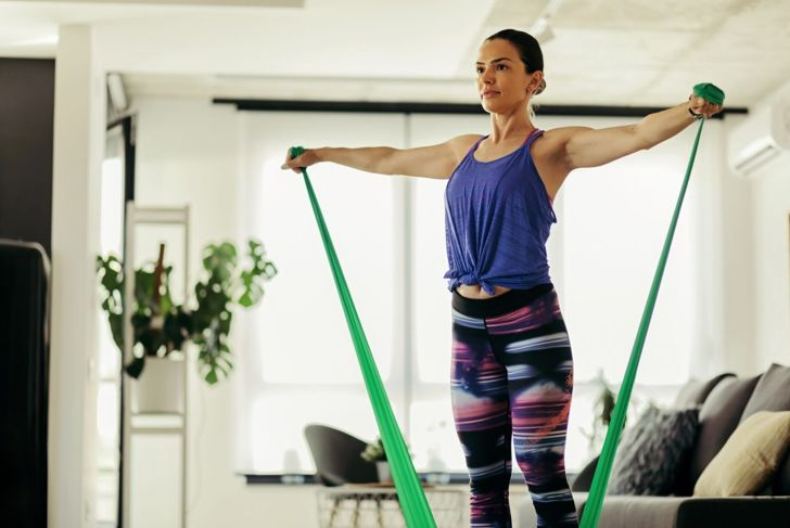 Woman exercising with a power band at home.