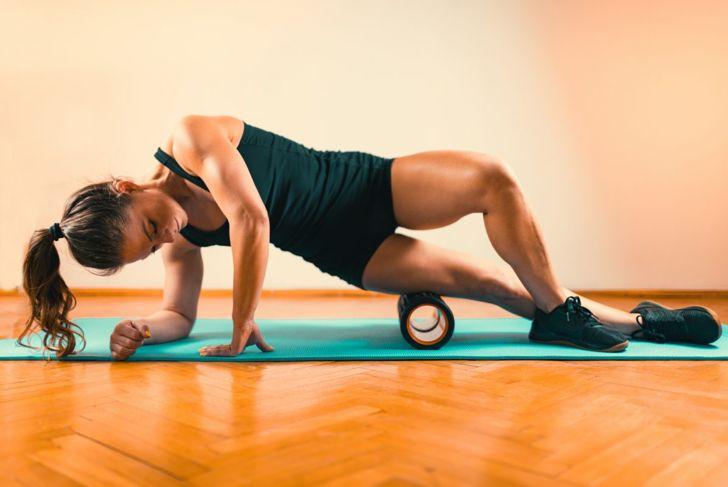 Woman massaging legs with foam roller.
