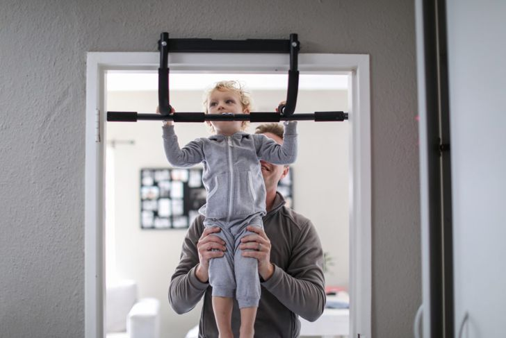 Man doing pull ups with chin up bar.