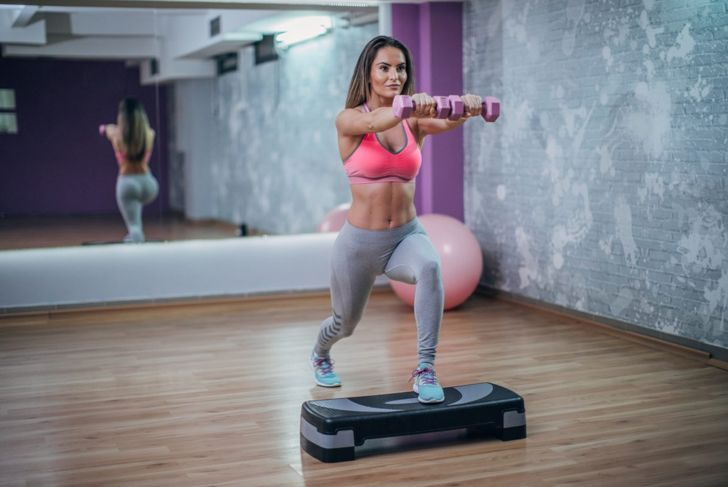Woman doing lunges with dumbbell on fitness block.