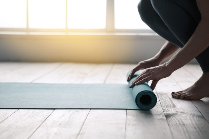Close up of woman's hands rolling up yoga mat on hard wood floor.