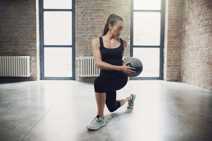Woman in lunge position holding medicine ball.
