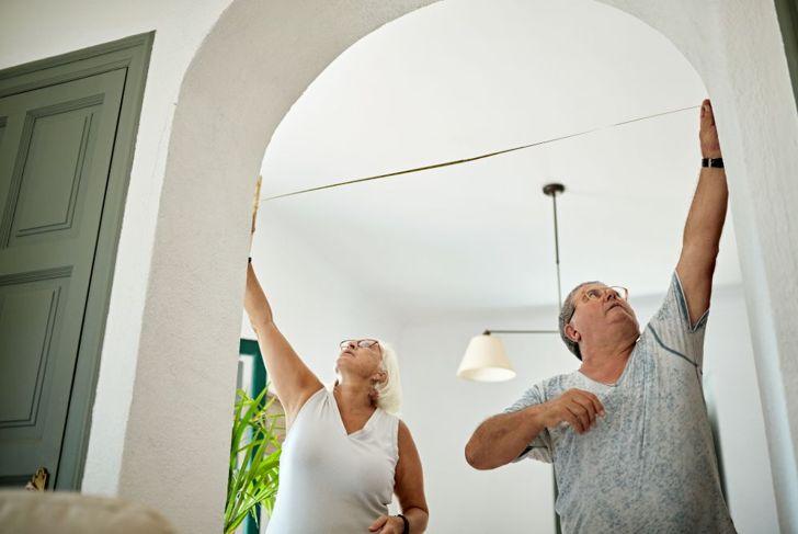 older man and woman measuring living room doorway