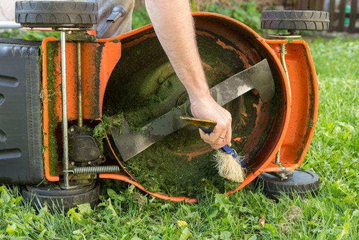 man cleaning around push lawn mower blade with brush