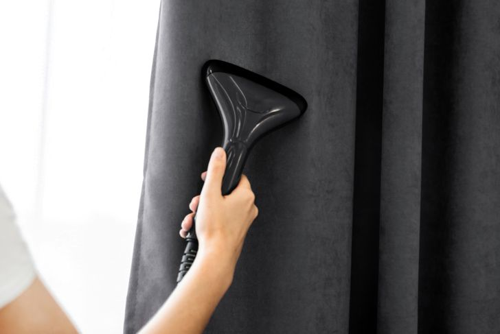 close up of a person steam cleaning curtains