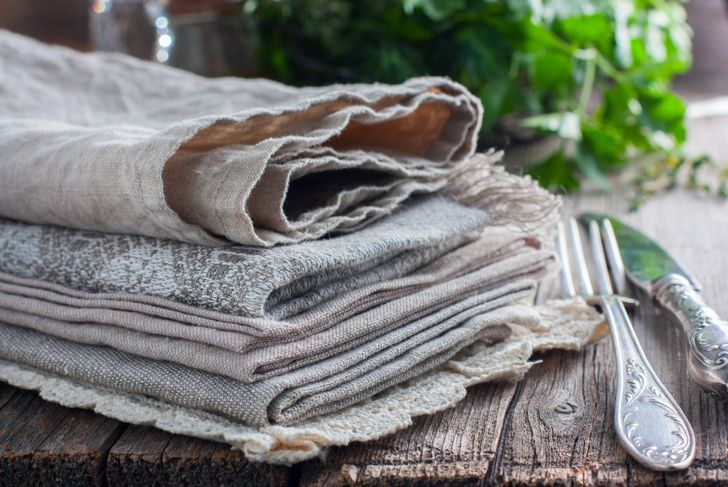 stack of table linens on rustic table