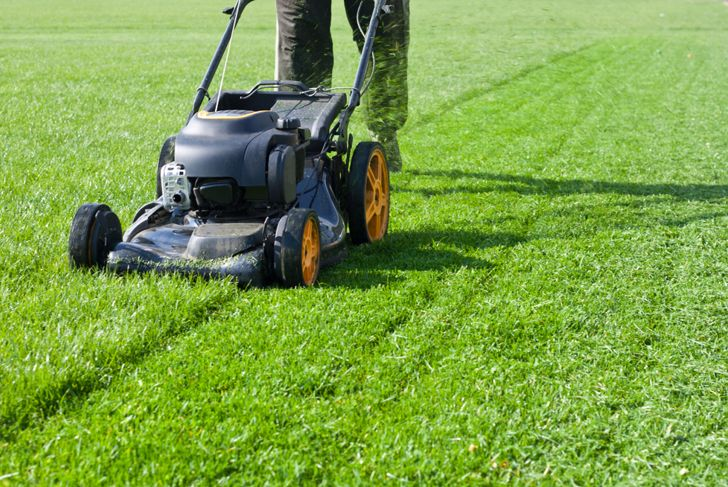 person mowing lawn with push mower