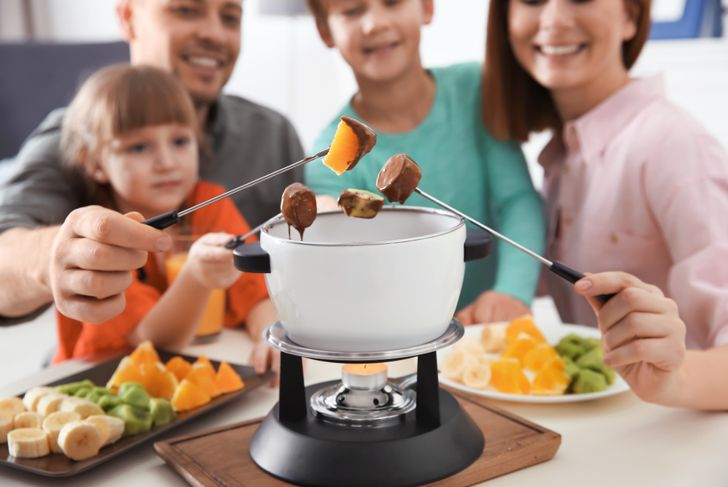 smiling family of four dipping fruit in a chocolate fondue