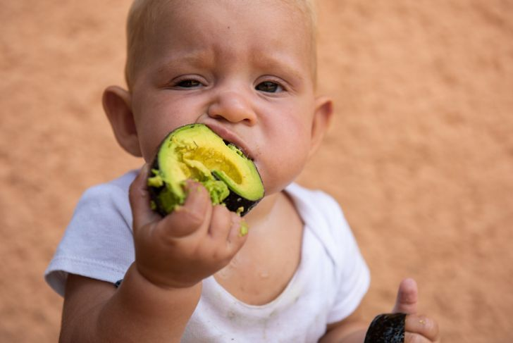 baby boy eating an avocado with messy hands