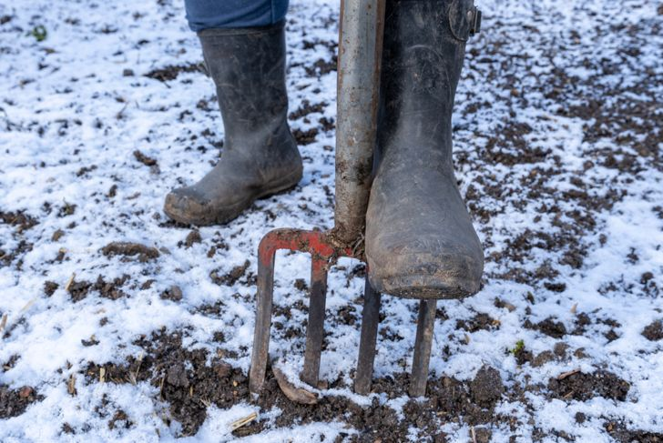 man in rubber boots pressing a pitchfork into frozen ground