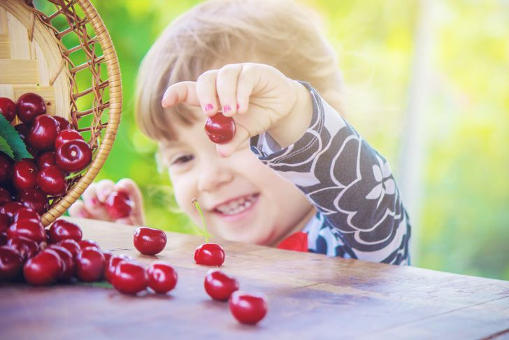 little girl outside picking up cherries from the table