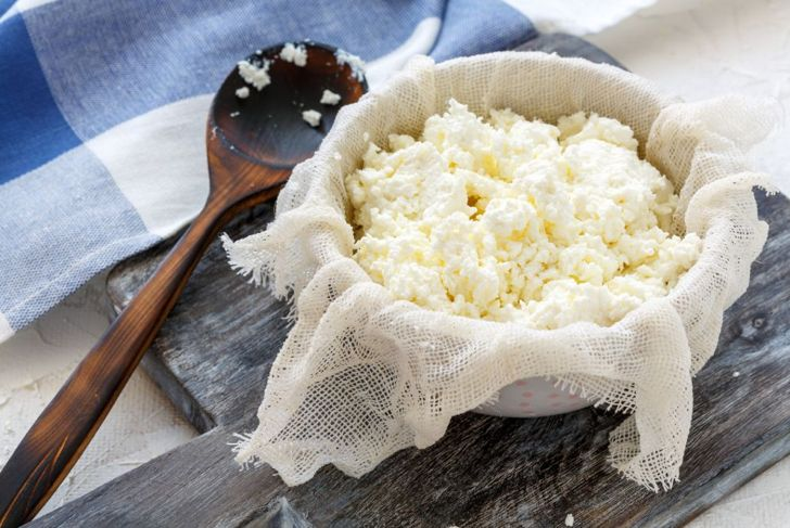 homemade cheese in cheesecloth on a wooden trivet