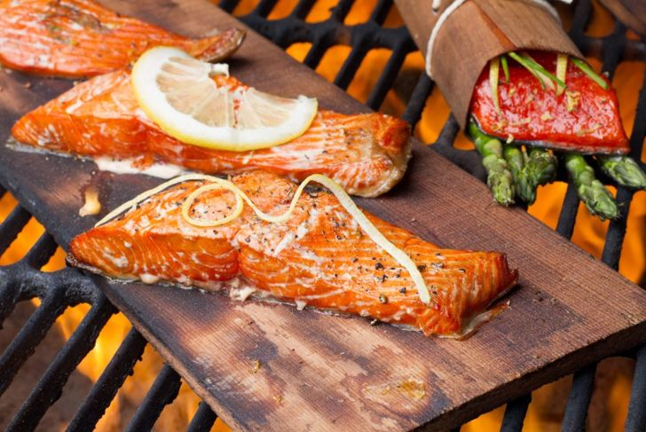 salmon cooking on a wood plank