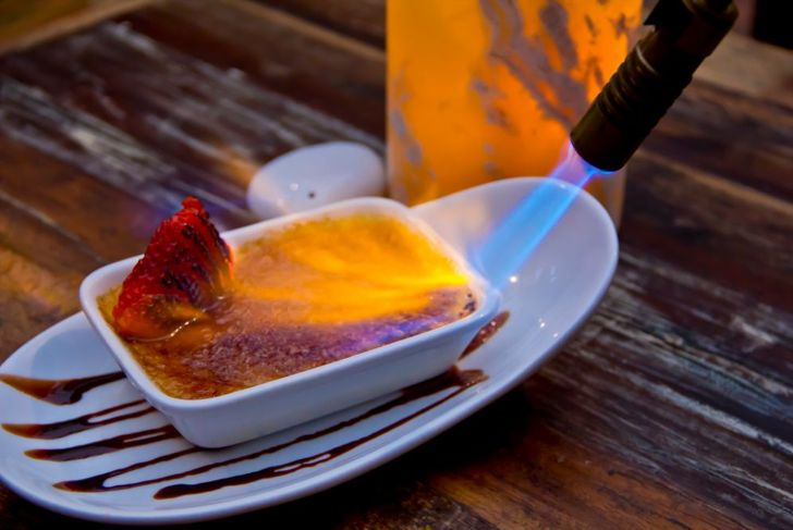 close up of a torch caramelizing the top of creme brulee dessert
