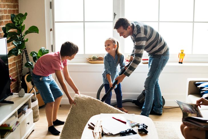 family vacuuming the living room together