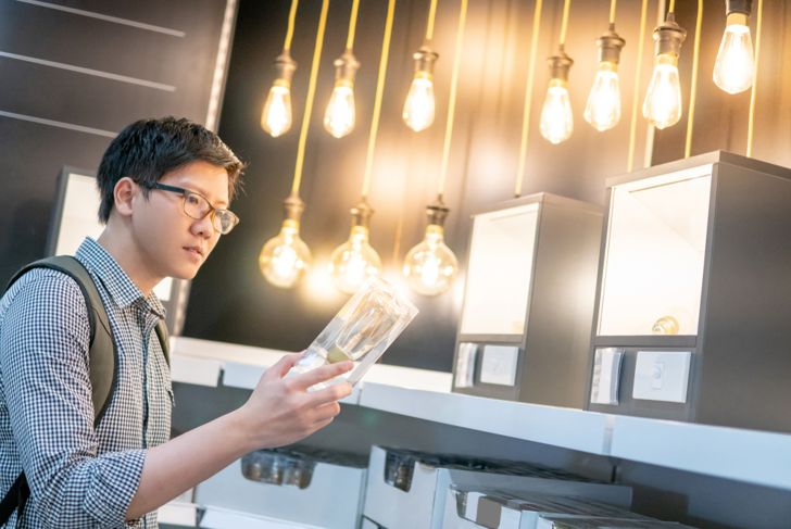 young man looking at lightbulb packages in store