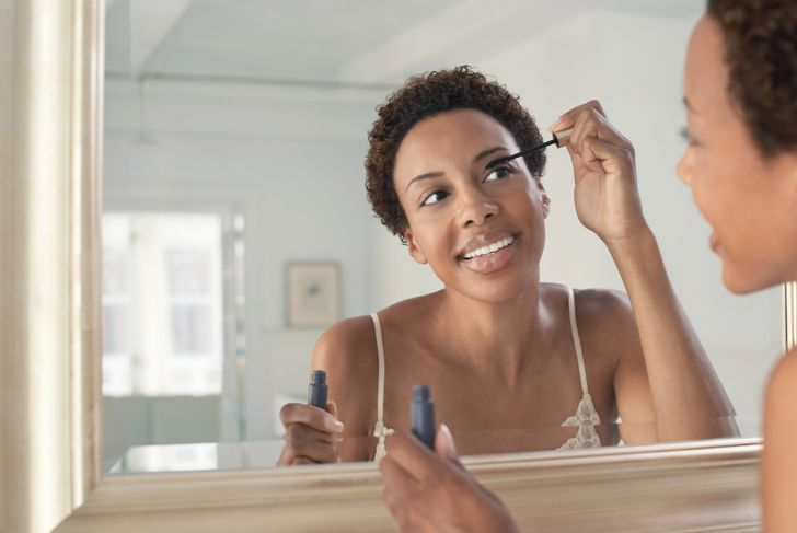 woman with type 4c hair applying makeup in mirror