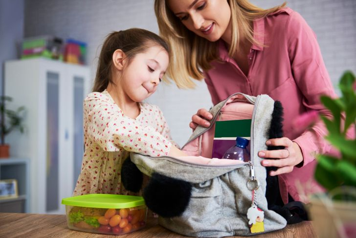 mom and little girl organizing school backpack