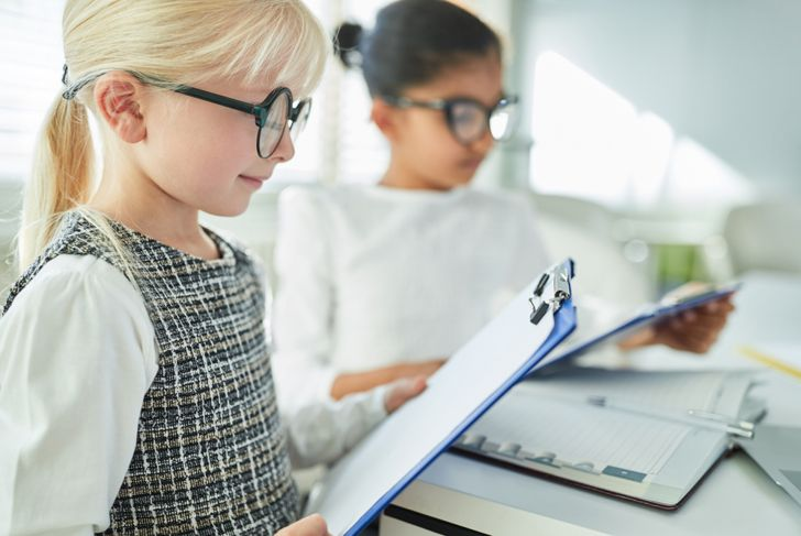 two little girls looking at checklists, dressed like businesswomen
