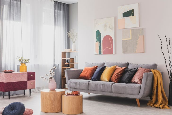 living room with large paintings as focal point behind couch