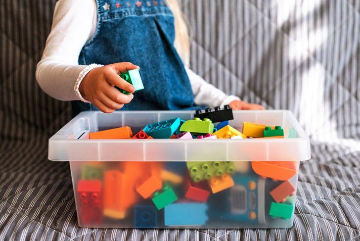 toddler girl putting away her toys in a bin
