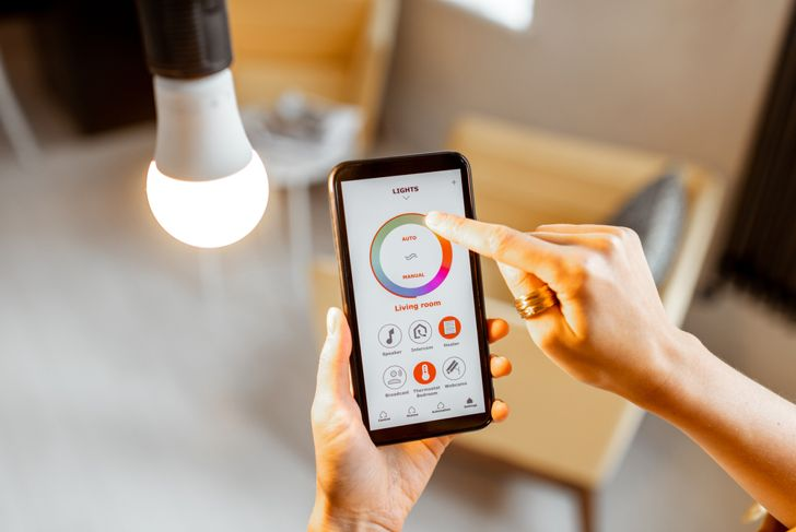 a woman is controlling her smart light with her cell phone