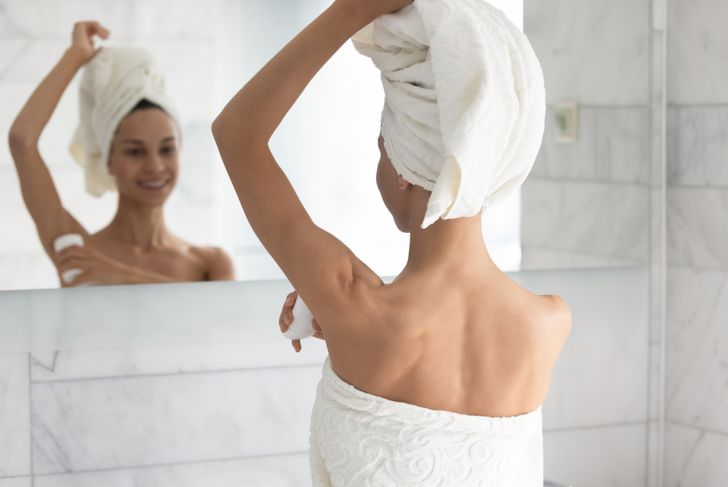 woman in bath towel applying deodorant