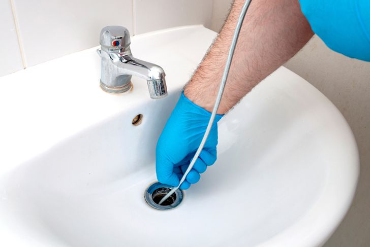 man with gloved hand putting wire drain snake down drain