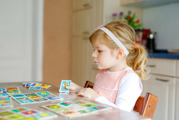 little girl playing a memory card game