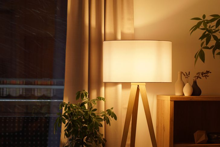 a floor lamp in a living room giving off a soft light